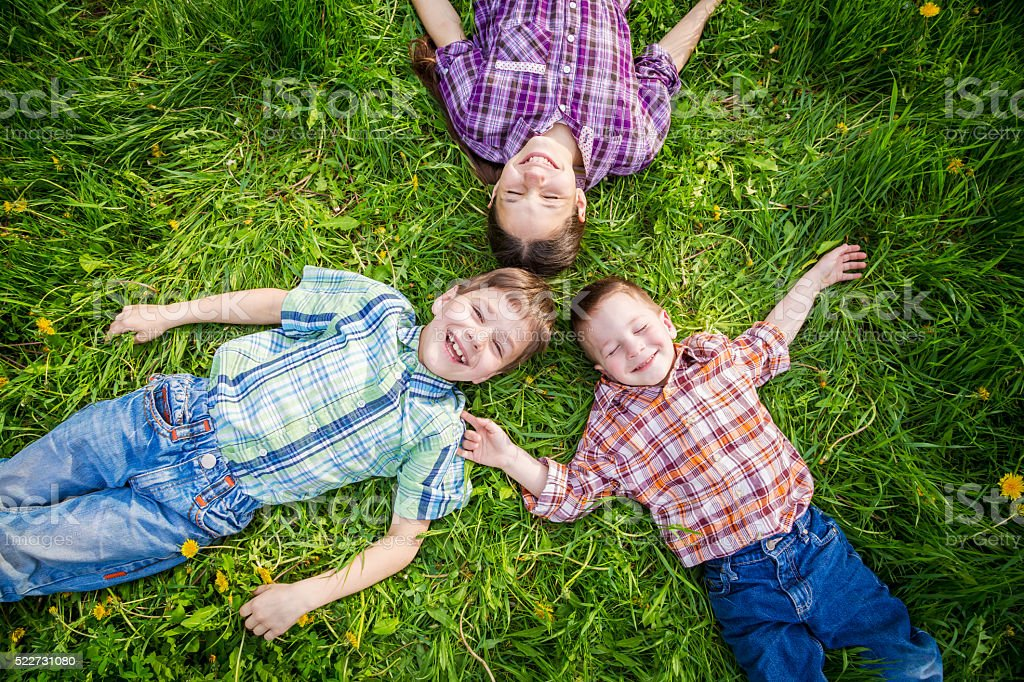 Three kids on grass with dandelions stock photo
