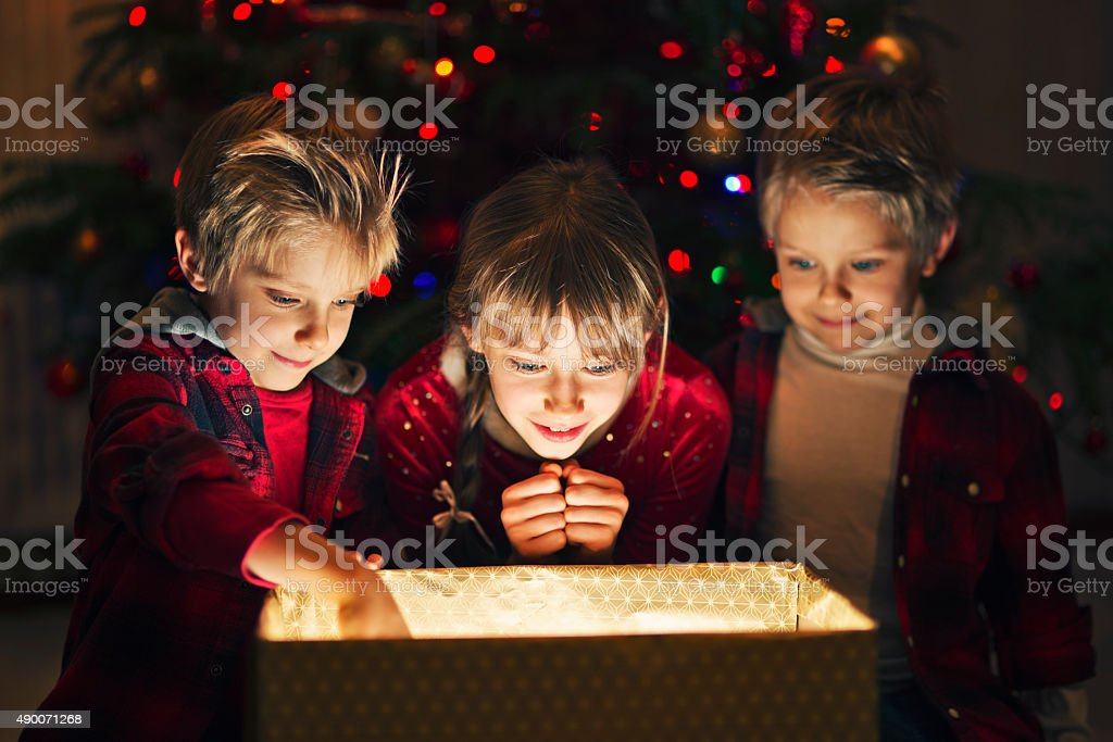 Three kids opening gift near the christmas tree stock photo