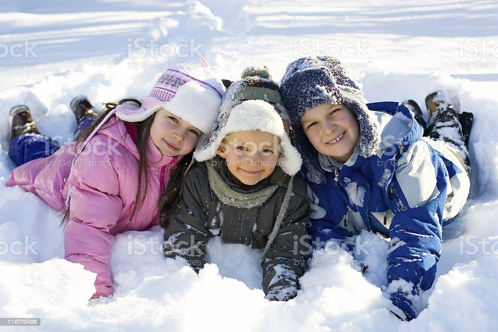 Three Kids Playing in Fresh Snow royalty-free stock photo