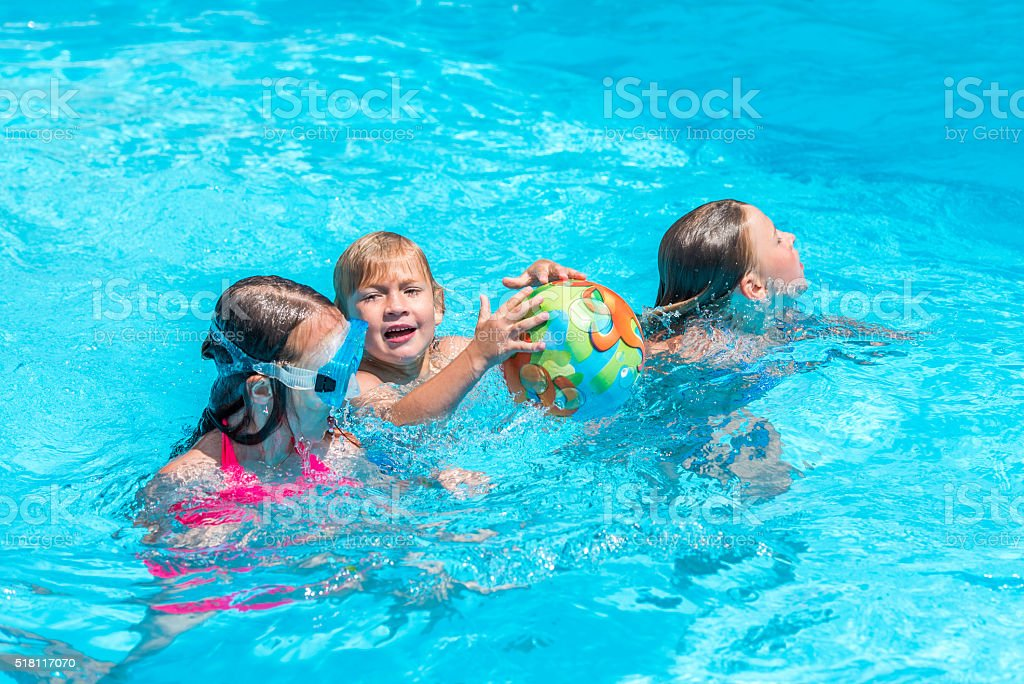 Three kids playing with a ball in the pool stock photo
