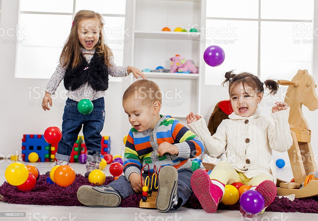 Three kids playing with toys in a room royalty-free stock photo