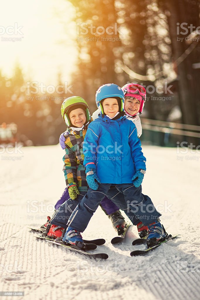 Three kids skiing on sunny winter day stock photo