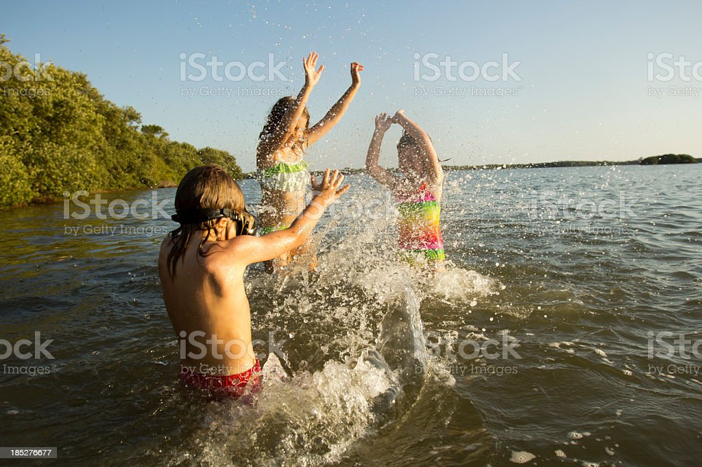 Three kids splashing in a lake stock photo