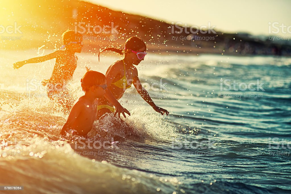 Three kids swimming and having fun at sea at sunset stock photo
