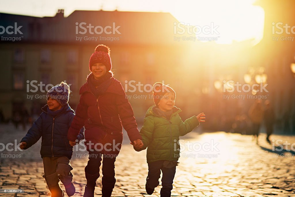 Three kids visiting Krakow old city in autumn stock photo