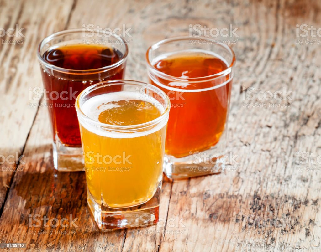 Three kinds of beer on old wooden background stock photo