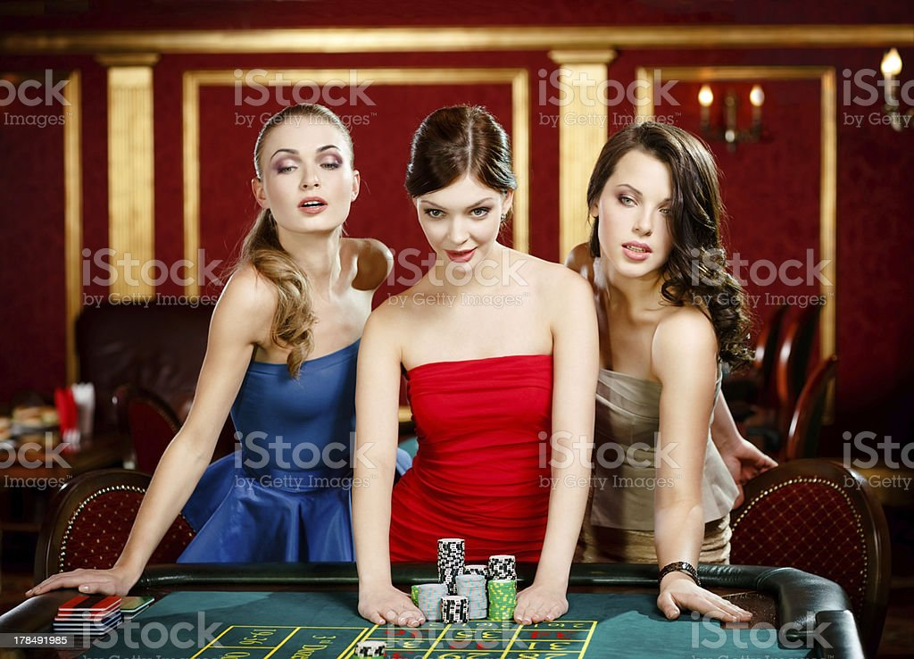 Three ladies place a bet playing roulette royalty-free stock photo