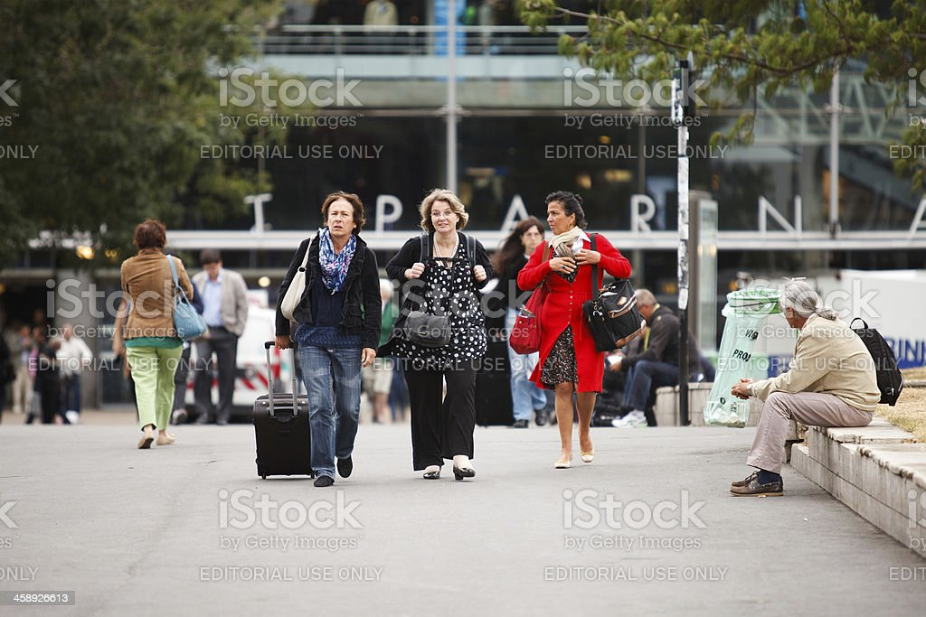 Three ladies walk away from train station stock photo