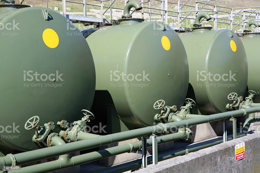 Three large green outdoor fuel tanks stock photo