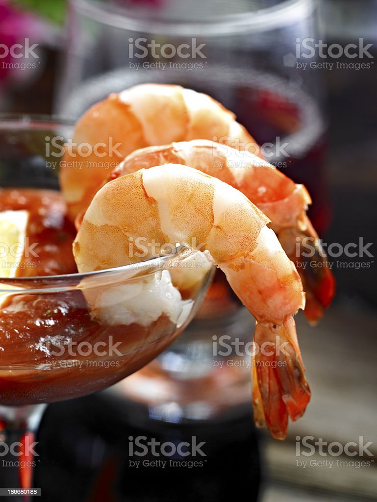 Three large shrimp hanging over glass in cocktail sauce stock photo