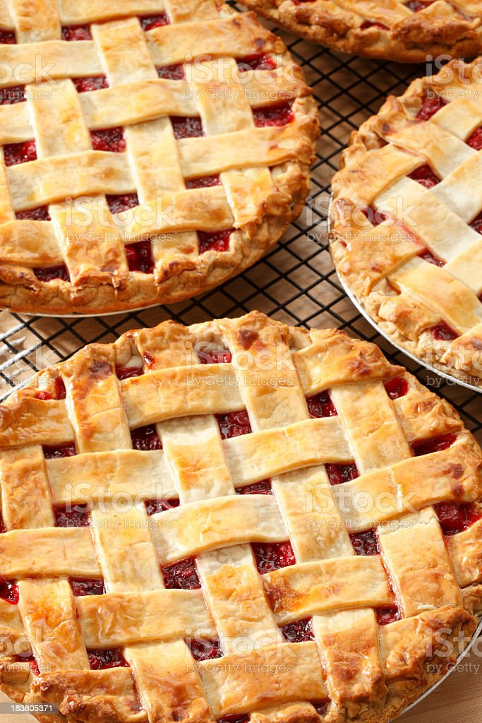 Three lattice topped cherry pies on a pie rack stock photo