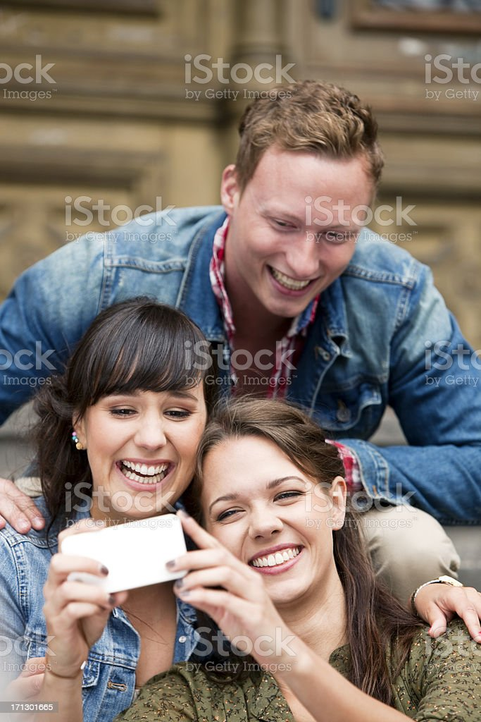Three Laughing Young People Taking Photo With Smartphone royalty-free stock photo