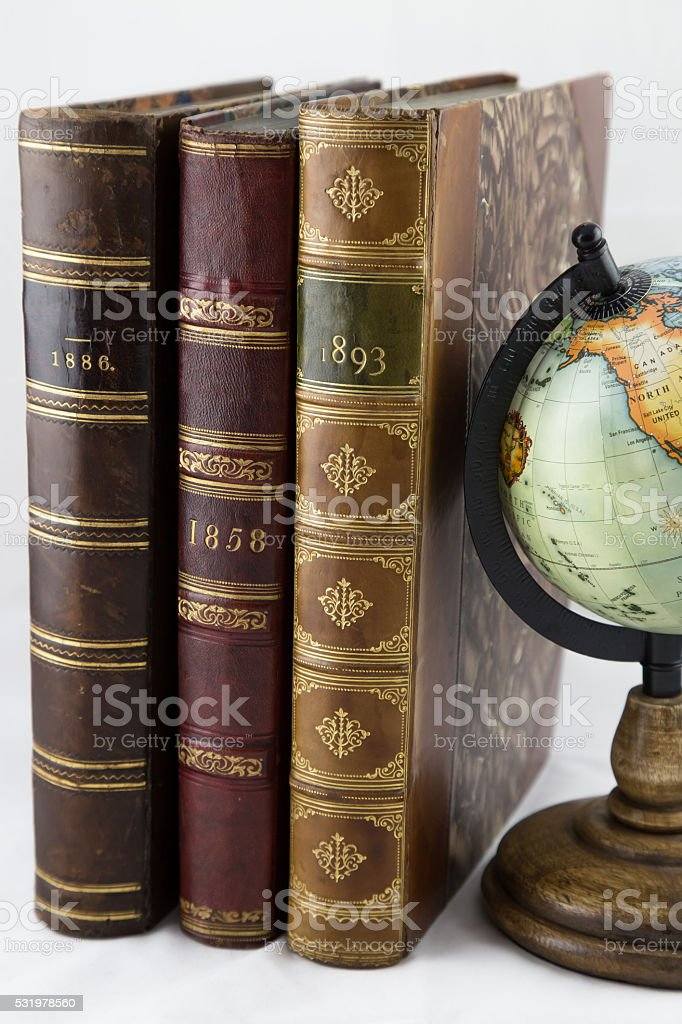 Three Leather Bound Antiquarian Books with Grey Background stock photo