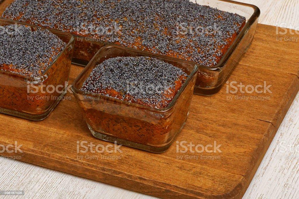Three lemon poppy cakes on wooden plate stock photo