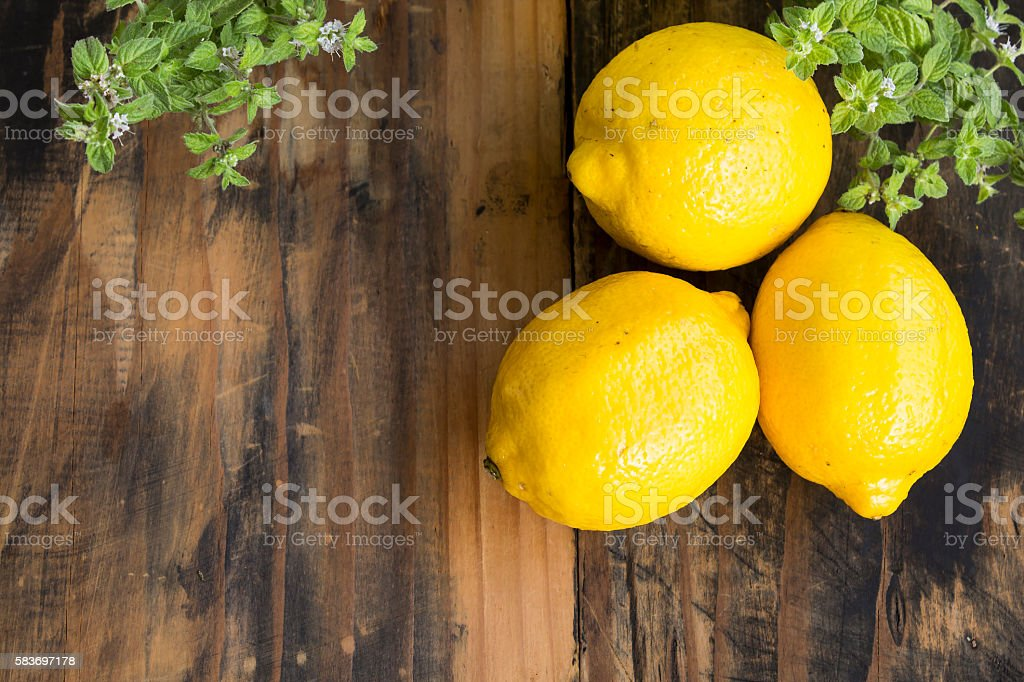 Three Lemons and Mint on a Rustic Wooden Background stock photo