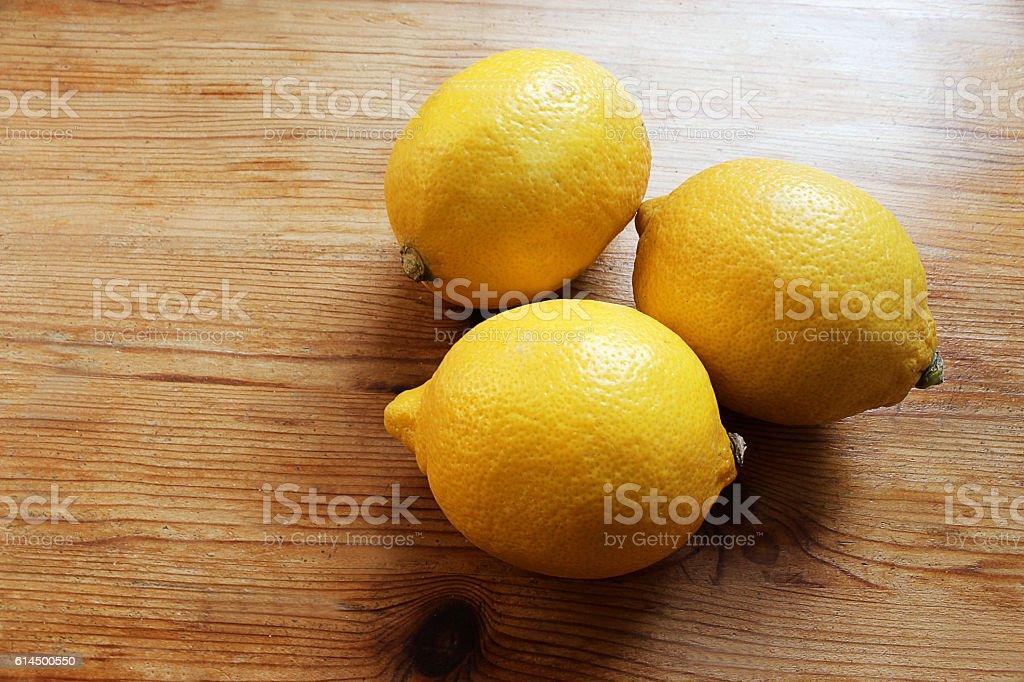 Three Lemons on a wooden Desk stock photo