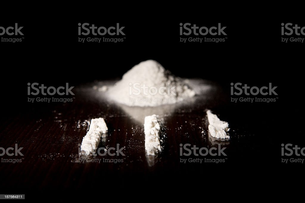 Three lines of cocaine next to a pile of it stock photo