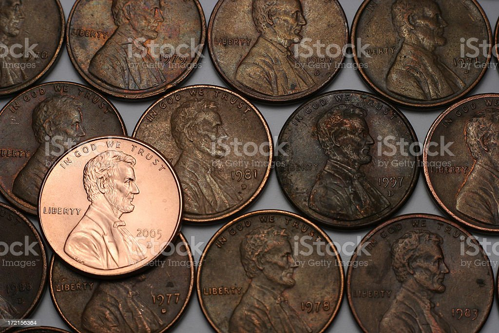 Three lines of old pennies and one shiny new one stock photo