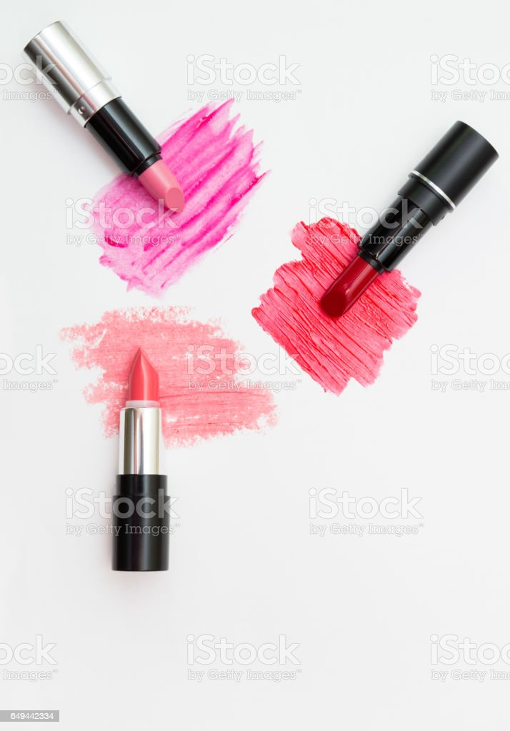Three lipsticks of different color with swatches. View from above stock photo