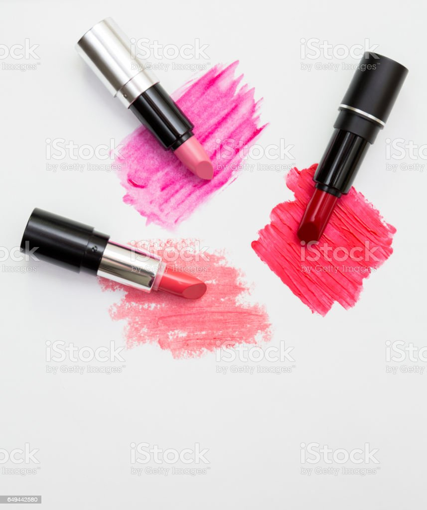 Three lipsticks with swatches on white background stock photo