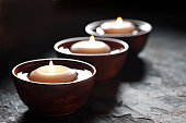 Three lit candles floating in wooden bowls filled with water