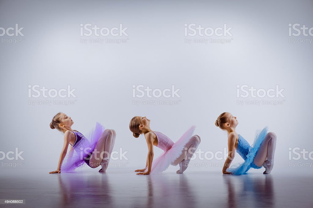 Three little ballet girls sitting in tutus and posing together stock photo