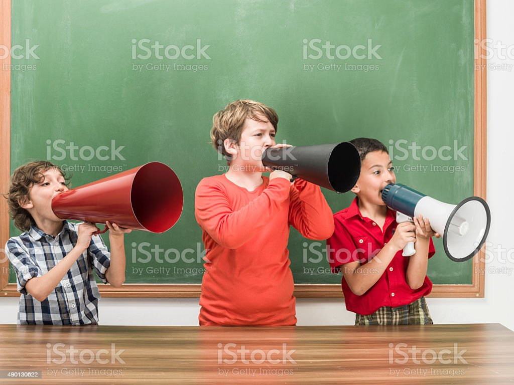 Three Little Boys Shouting With Megaphones In Front Of Blackboard stock photo