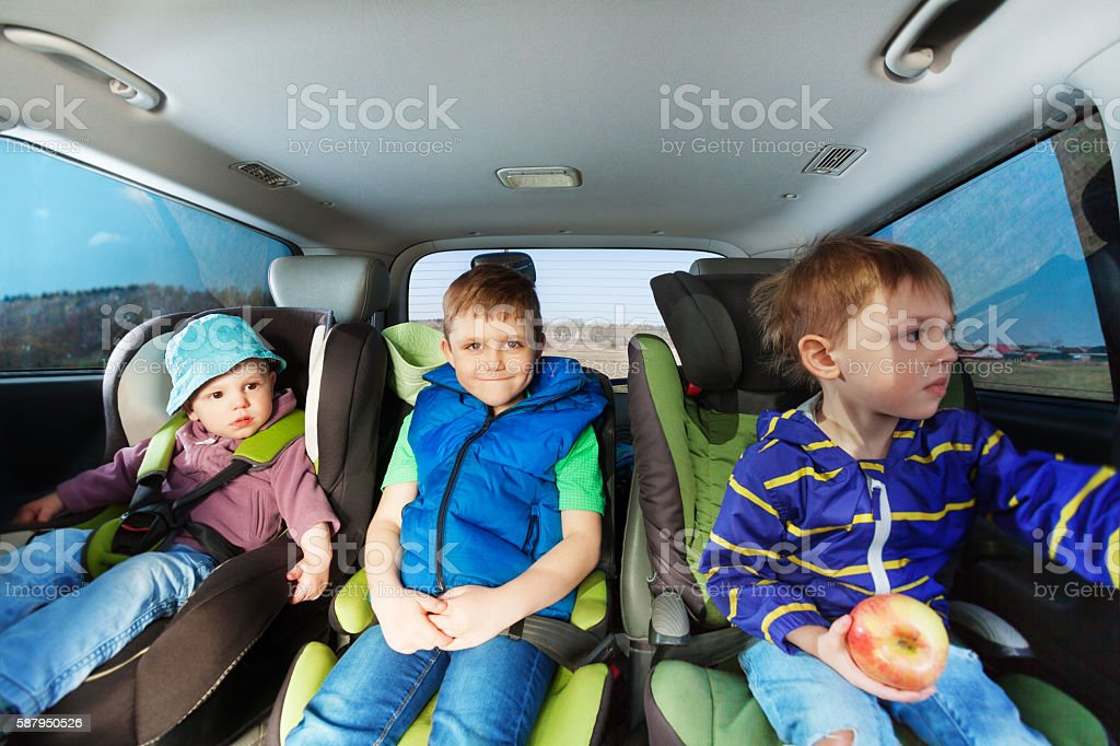 Three little boys sitting in safety car seats stock photo