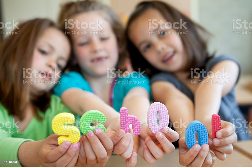 """Three little girls with the word """"school"""" royalty-free stock photo"""