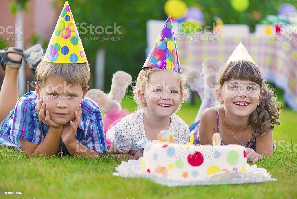 Three little kids celebrating birthday royalty-free stock photo