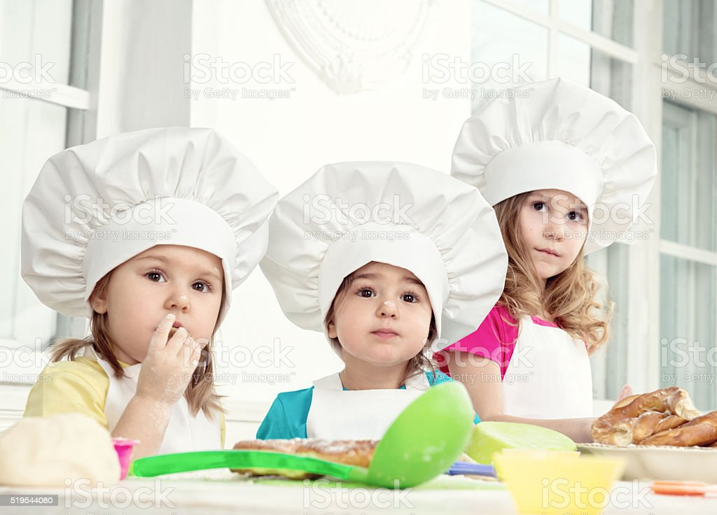 Three Little Sisters Making Dough For Baking stock photo