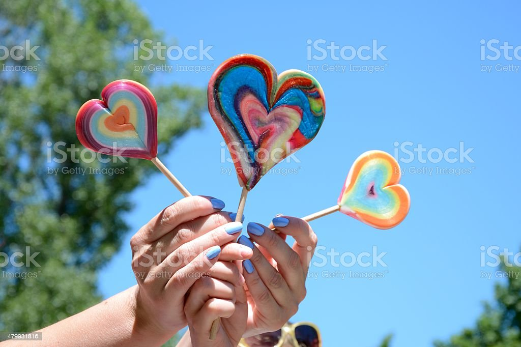 Three lollipops in woman's an kid's hands stock photo