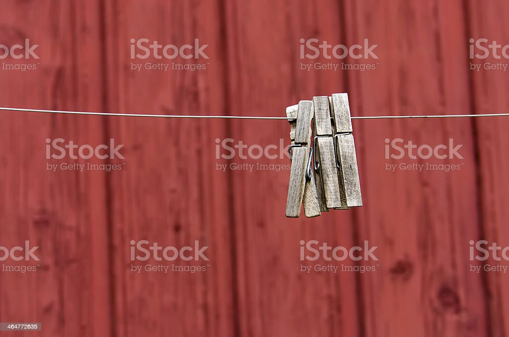 Three lone clothespins on red wall background royalty-free stock photo
