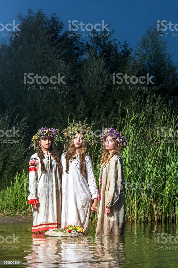 Three lovely nymphs in river at night stock photo