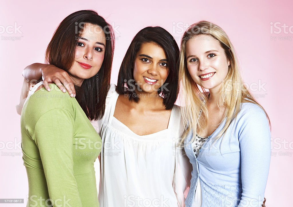 Three lovely young women smiles and hug each other stock photo