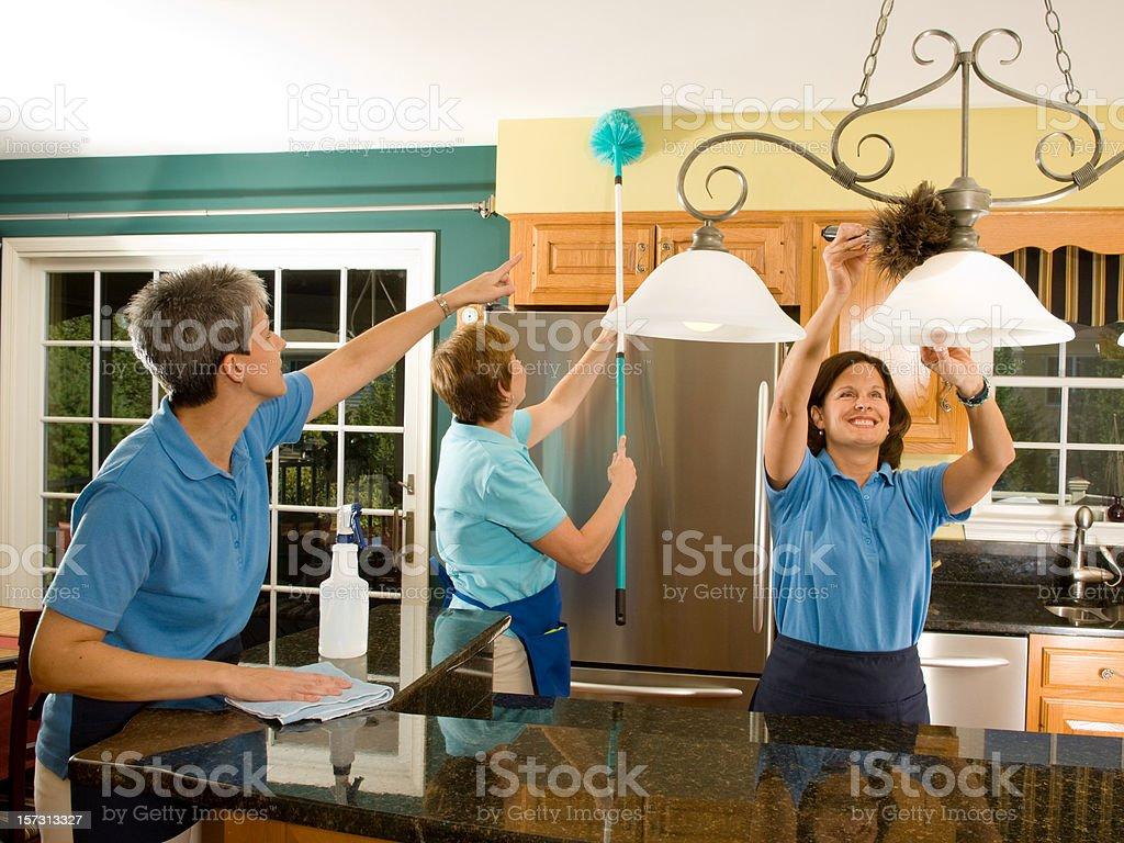 Three Maids Cleaning Kitchen stock photo