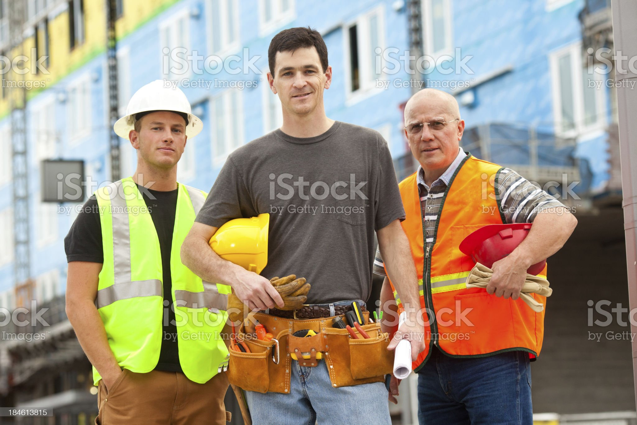 Three male construction workers at building site royalty-free stock photo