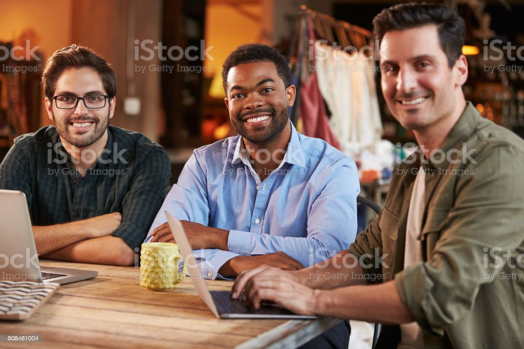 Three Male Fashion Designers In Meeting Using Laptop stock photo