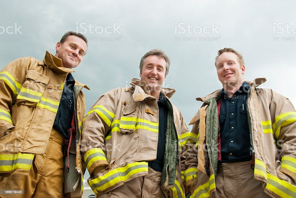 Three male firefighters in their work clothes smiling royalty-free stock photo