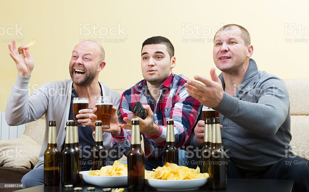 Three male friends sitting at table with beer stock photo