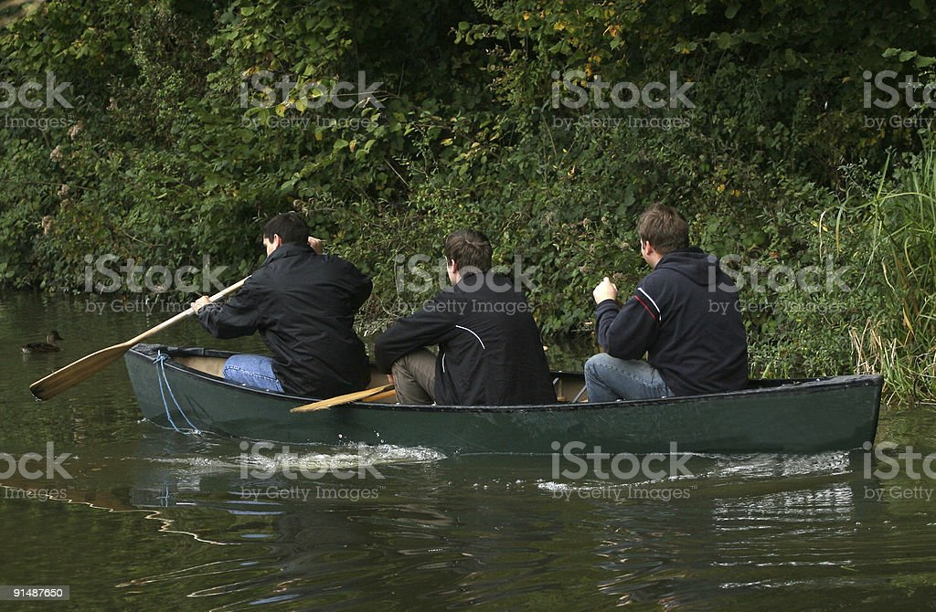Three male teenagers having fun canoeing down a river royalty-free stock photo