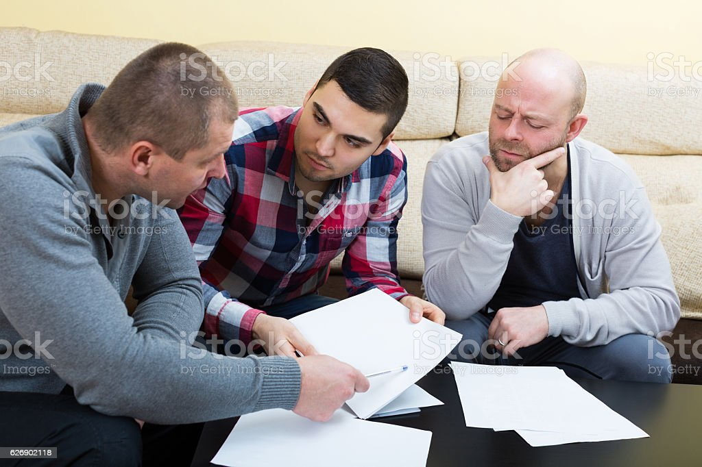 Three males with documents stock photo