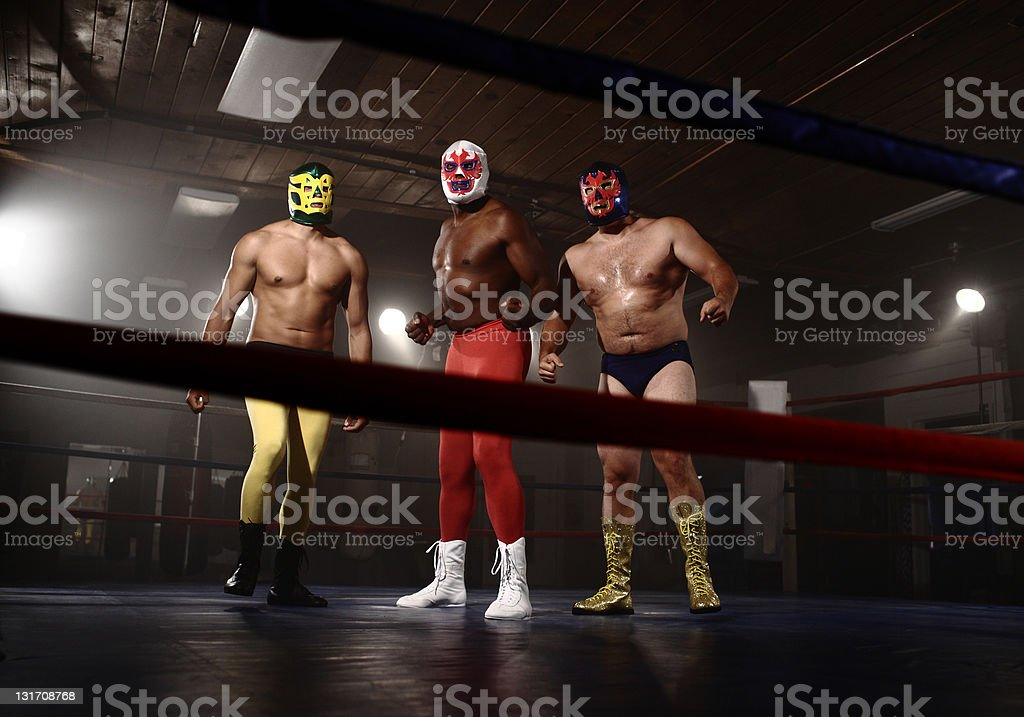 Three masked wrestlers in ring royalty-free stock photo