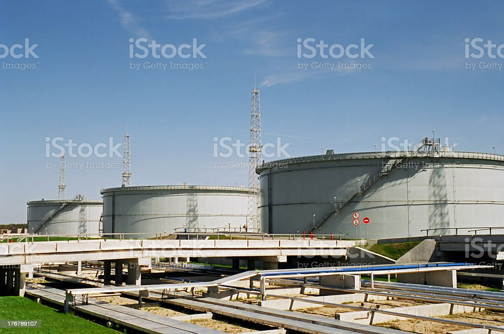 Three massive fuel storage tanks with surrounding facilities royalty-free stock photo