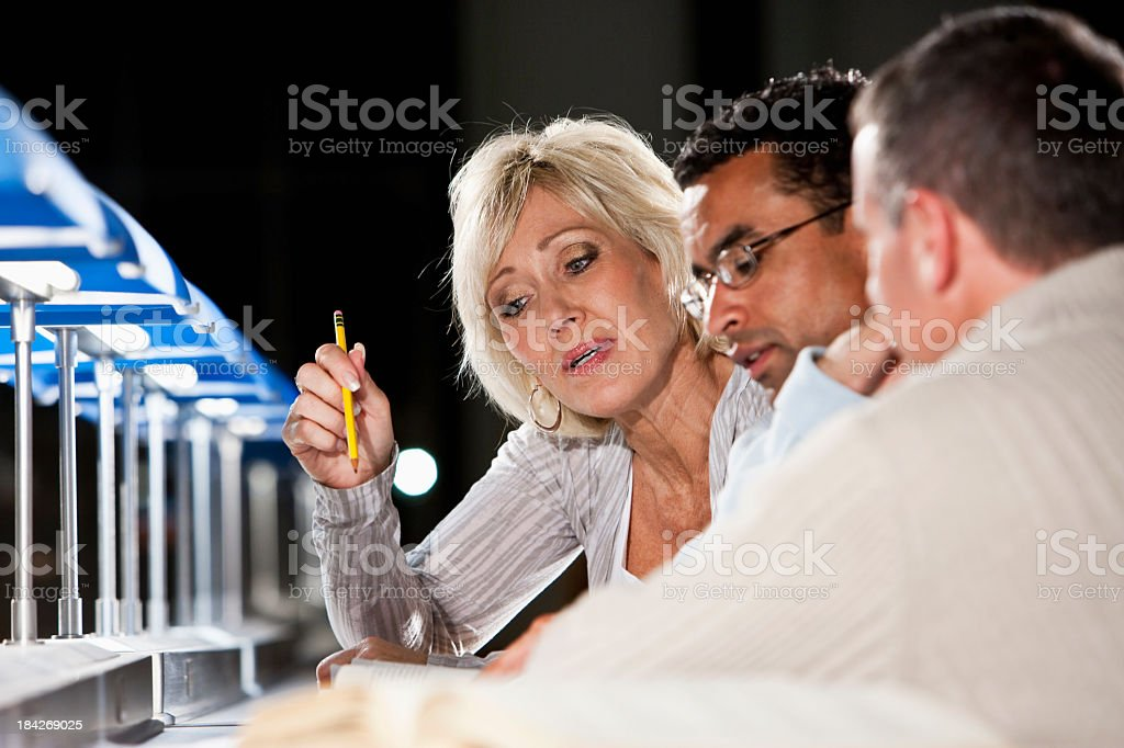Three mature adults working late on a project stock photo
