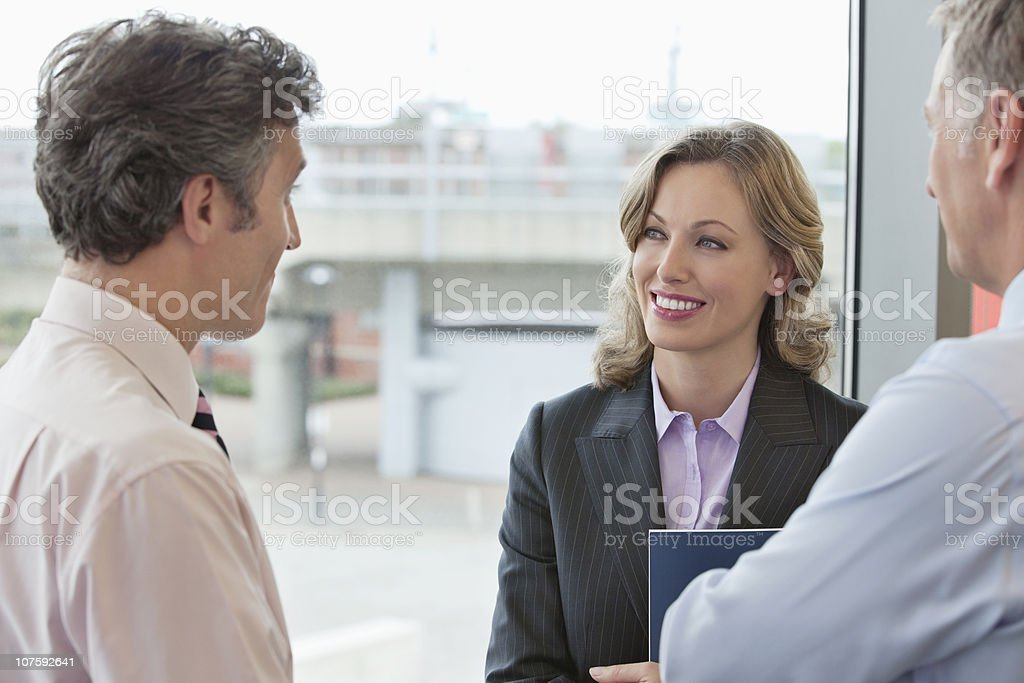 Three mature business people having a meeting near bay window in office royalty-free stock photo