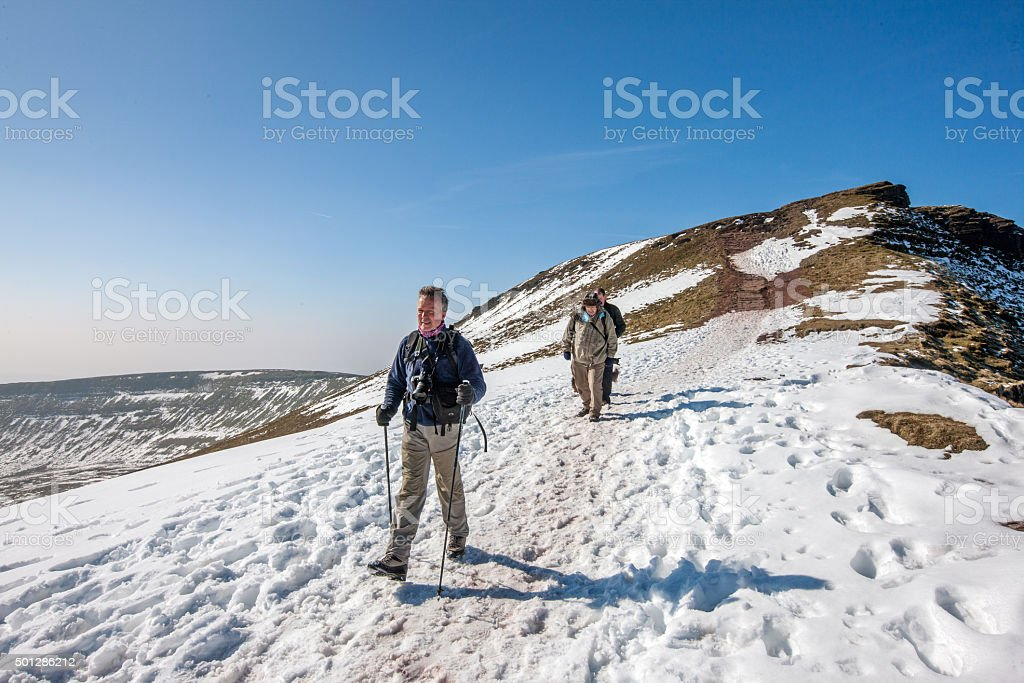 Three mature walkers on snow covered mountain stock photo