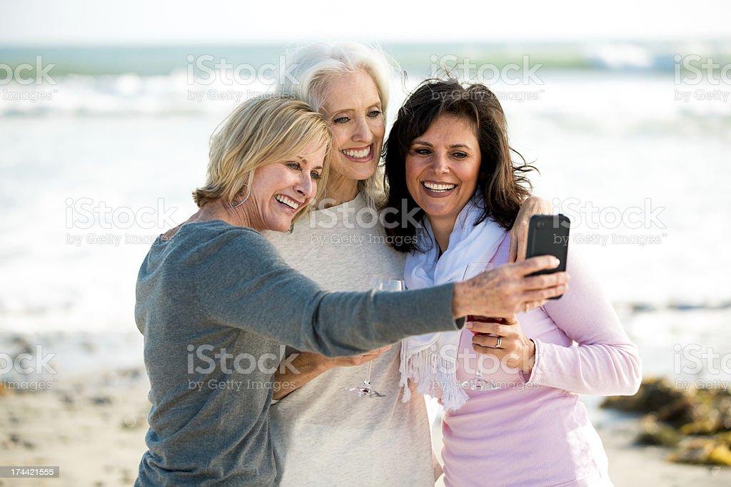 Three mature women at the beach taking selfie stock photo