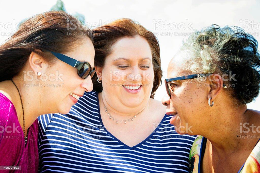Three mature women having fun gossiping outdoors stock photo