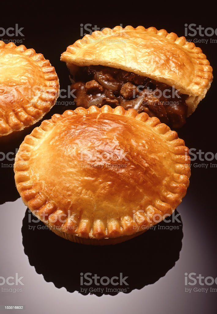 Three meat pies with one half eaten stock photo